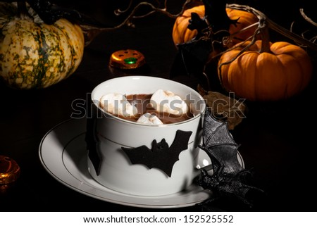 Cup of hot chocolate with ghost marshmallow, surrounded with pumpkins, candles, and Halloween decoration. Halloween drinks series.  - stock photo