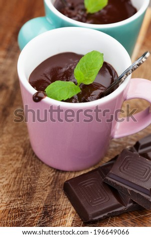 Cup of hot chocolate with mint on old wooden table, selective focus - stock photo