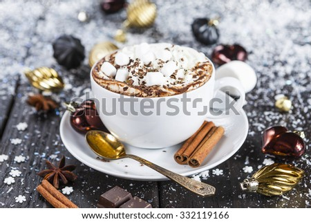 Cup of hot chocolate with whipped cream and marshmallows on snowy table - stock photo