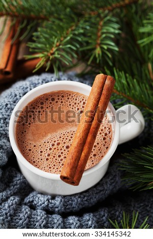 Cup of hot cocoa or hot chocolate on knitted background with fir tree and cinnamon sticks, traditional beverage for winter time - stock photo