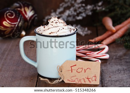 "Cup of hot cocoa with whipped cream and chocolate shavings. Note that reads ""For Santa"" and carrots in the background for Santa's reindeer. Extreme shallow depth of field with focus on tag."