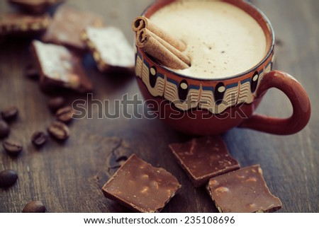 Cup of hot coffe with cinnamon sticks on vintage wooden background, selective focus - stock photo