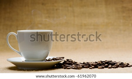 Cup of hot coffee about the ferry and grains of coffee on grunge a background. Old tone - stock photo