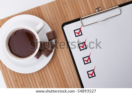 Cup of hot coffee and checklist on clipboard - stock photo
