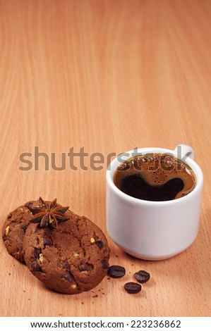 Cup of hot coffee and chocolate chip cookies on the desk