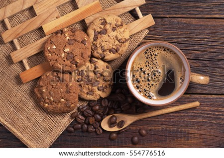 Cup of hot coffee and chocolate cookies for breakfast on wooden table, top view