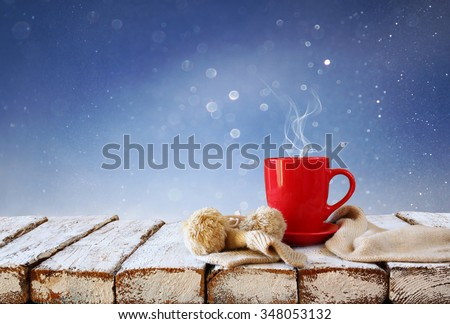Cup of hot coffee and cozy knitted scarf on wooden table in front of glitter background - stock photo