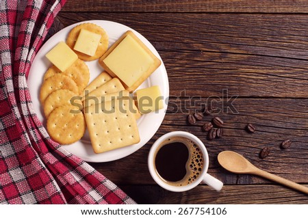 Cup of hot coffee and crackers with cheese on rustic wooden table, top view - stock photo