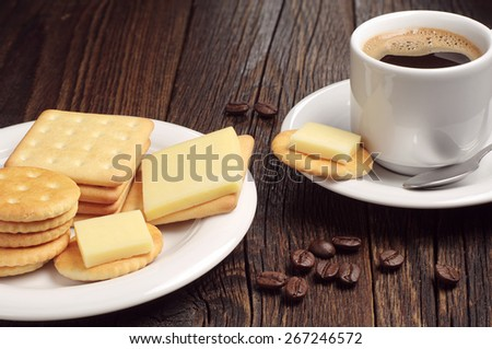 Cup of hot coffee and crackers with cheese on wooden table - stock photo