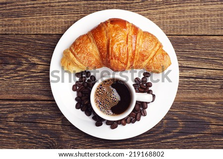 Cup of hot coffee and croissant on vintage wooden table. Top view - stock photo