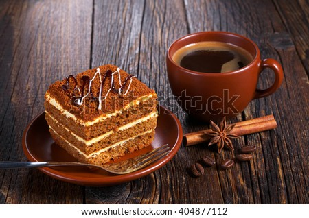 Cup of hot coffee and honey cake on dark wooden table - stock photo