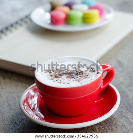 Cup of hot coffee and macaroons