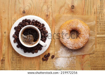 Cup of hot coffee and sweet donut on wooden background. Top view - stock photo