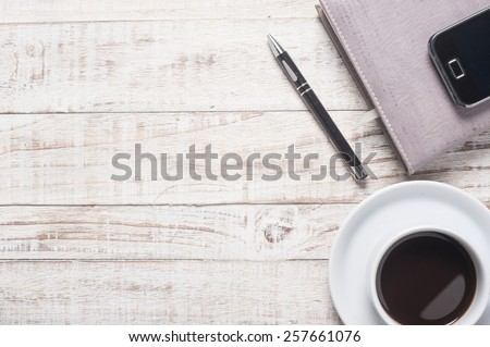 Cup of hot coffee and white note book on wood table - stock photo