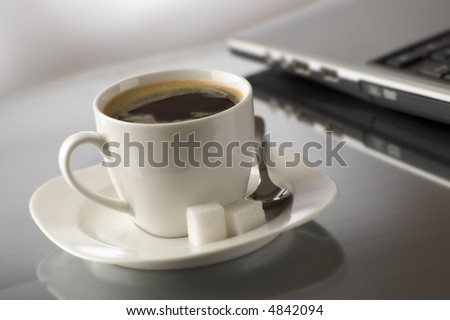 cup of hot coffee beside a laptop close up - stock photo