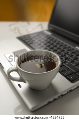 cup of hot coffee on a  laptop close up