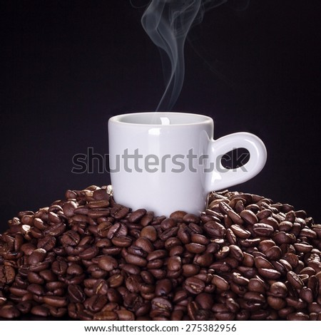 Cup of hot coffee on top of coffee beans with black background - stock photo