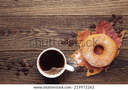 Cup of hot coffee, sweet donut and autumn leaves on a wooden table. Top view - stock photo