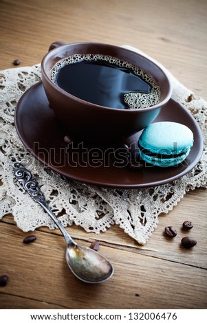 Cup of hot coffee with french macaroon