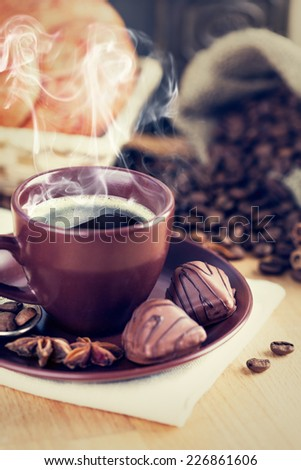 Cup of hot coffee with smoke steam and chocolate candies - stock photo