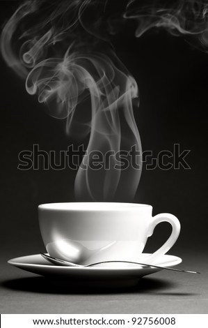 Cup of hot coffee with steam on dark background. Monochrome image. - stock photo