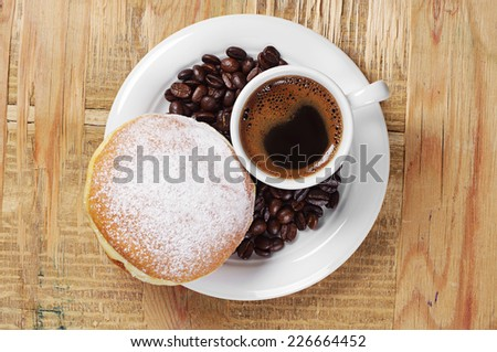 Cup of hot coffee with sweet doughnut on old wooden table. Top view - stock photo