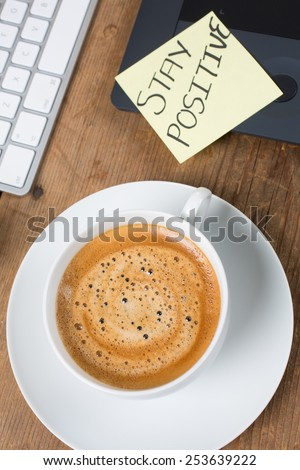 Cup of hot delicious coffee with computer keyboard on a rustic table and stay positive note