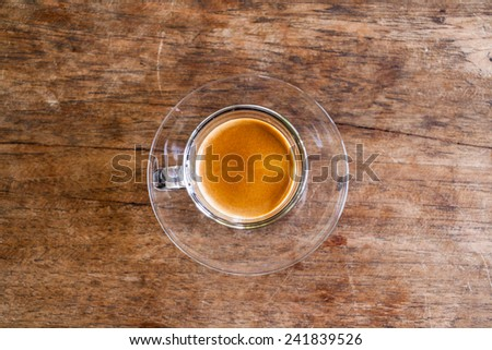 Cup of hot espresso coffee on wooden table. - stock photo