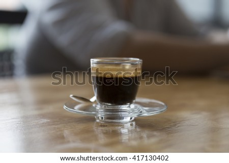 cup of hot espresso coffee shot on wooden table - stock photo
