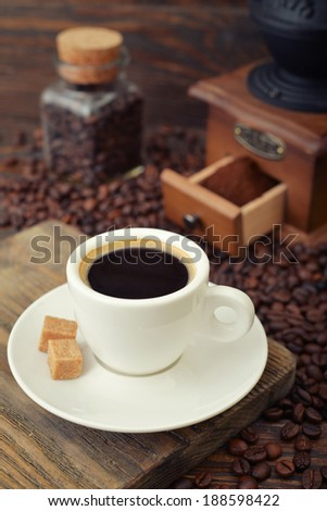 Cup of hot espresso with  vintage coffee grinder on wooden background