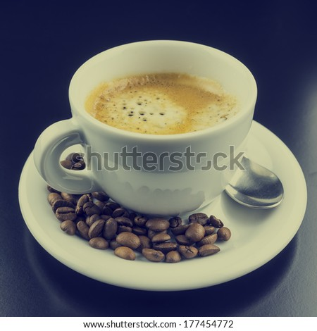 Cup of hot frothy strong full roast espresso coffee with roasted coffee beans in the saucer, close up on a black background. With retro filter effect. - stock photo