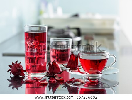 Cup of hot hibiscus tea (rosella, karkade, red sorrel) and the same cold drink with ice in glass on kitchen table. Drink made from magenta calyces (sepals) of roselle flowers. - stock photo