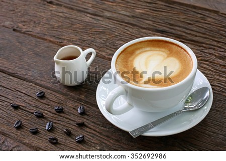Cup of hot latte art coffee and syrup in small cup on old wooden table - stock photo