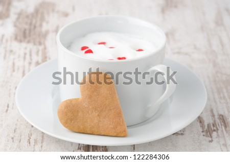 cup of hot milk with foam, decorated with sugar hearts and heart-shaped cookies on the table - stock photo