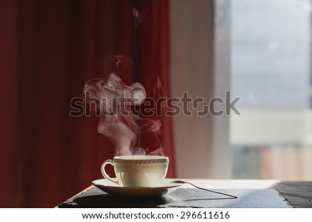 Cup of hot morning coffee with steam on dark background at home - stock photo