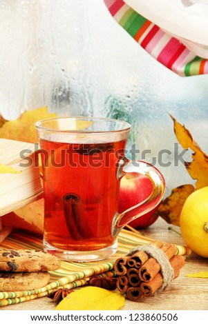 cup of hot tea and autumn leaves, on wooden table - stock photo