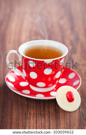 Cup of hot tea and white chocolate cranberries candy, selective focus - stock photo
