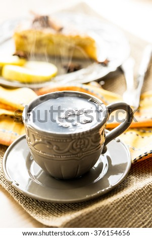 Cup of hot tea in a vintage cup and apple tart on the background - stock photo