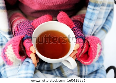 Cup of hot tea in child girl's hands - stock photo