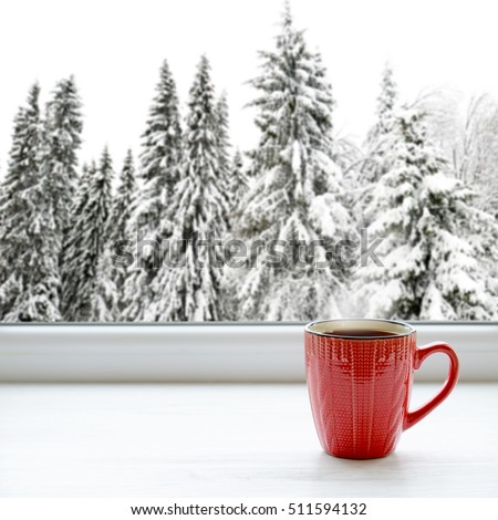 Cup of hot tea on a window sill. In the background, a beautiful winter forest in snow
