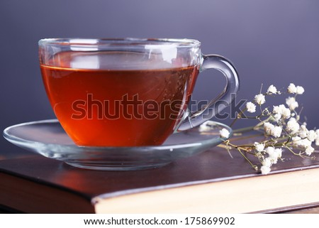 Cup of hot tea on book with flowers on table on gray background