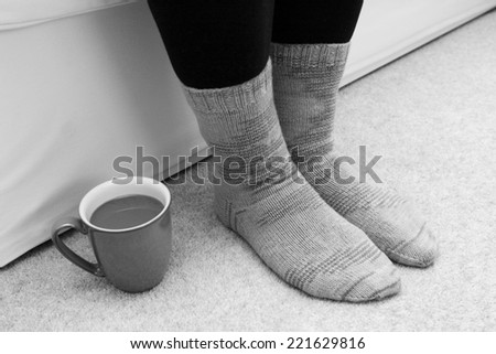 Cup of hot tea or coffee on the floor by a woman's feet in knitted socks - monochrome processing - stock photo