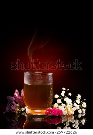 Cup of hot tea. Tea Steam. Flowers near. Red Spotlight on black background - stock photo