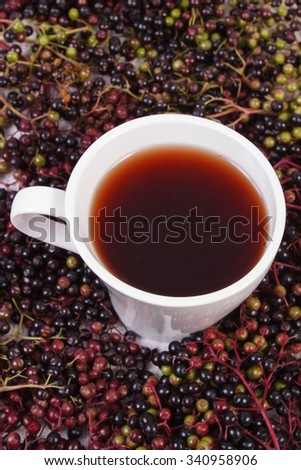 Cup of hot tea with elderberry juice and heap of berry in background, healthy nutrition, alternative medicine and therapy - stock photo