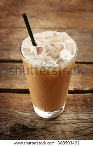 Cup of ice coffee with straw on wooden background - stock photo