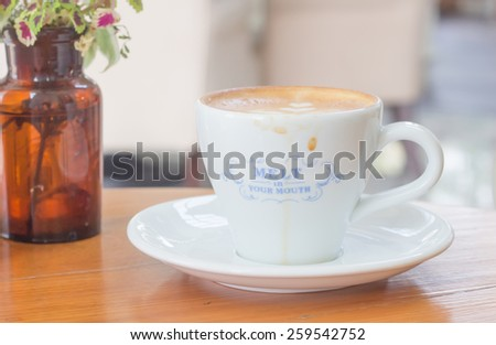 Cup of Latte coffee on the wooden desk - stock photo