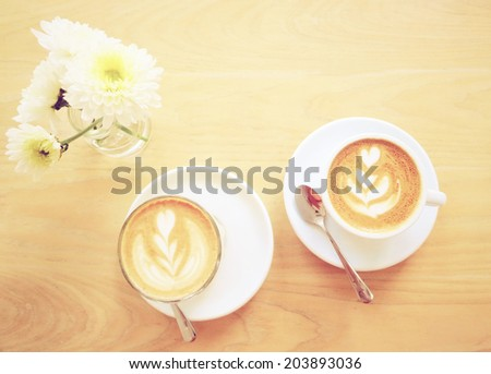 Cup of latte or cappuccino coffee and flower with retro instagram filter effect  - stock photo