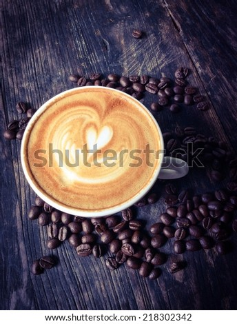 Cup of latte or cappuccino on wooden desk with coffee beans  - stock photo