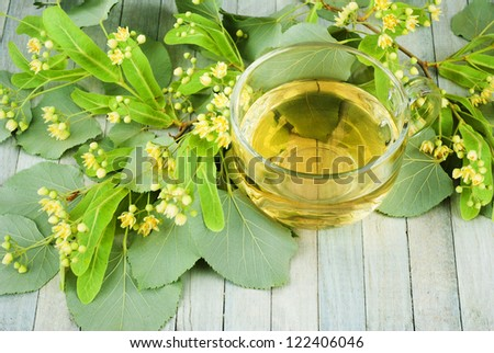 cup of lime tree tea and lime tree blossoms, bright wooden table