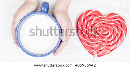 Cup of milk in child hands, top view closeup - stock photo
